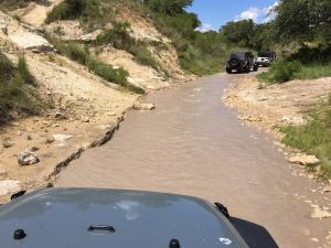 Jeep going up a creek towards waterfalls